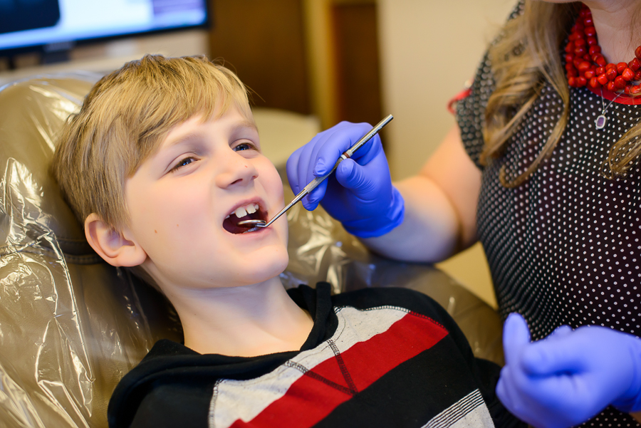 Young patient who came in for Woodland Family Dental's kids dentistry treatment is getting an exam by Dr. Sunnshine.