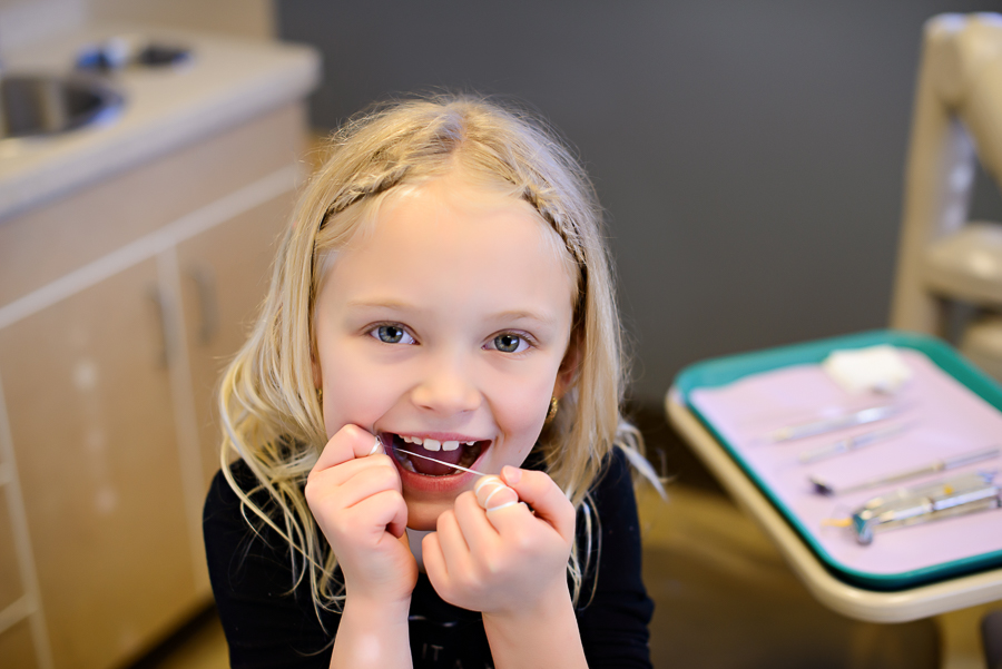 Image of a young patient flossing and waiting to see if she is a candidate for early orthodontic treatment at Woodland Family Dental.
