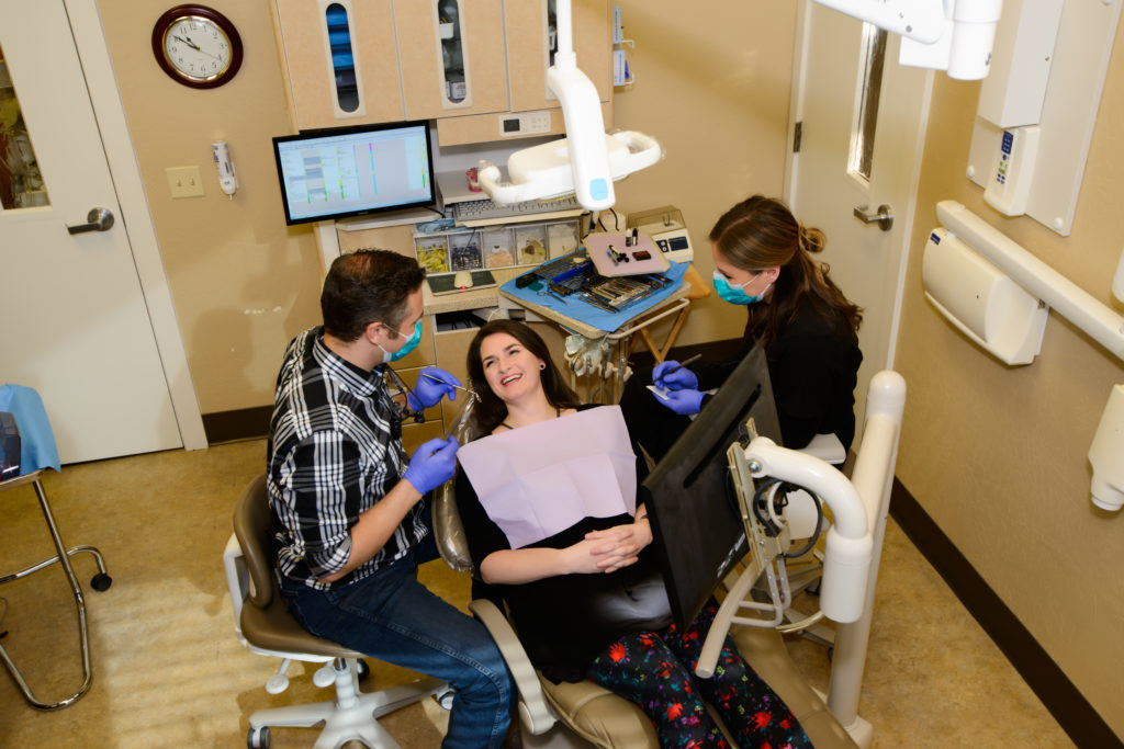 Dr. David begins treatment with a patient receiving dental implants at Woodland Family Dental to help her restore her smile.