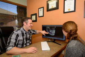 Dr. David consults with a patient via a digital x-ray at Woodland Family Dental to show how veneers will enhance and close the gaps in her smile.
